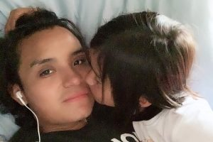 Salomon Diego Alonso lies in bed while his small daughter kisses his cheek