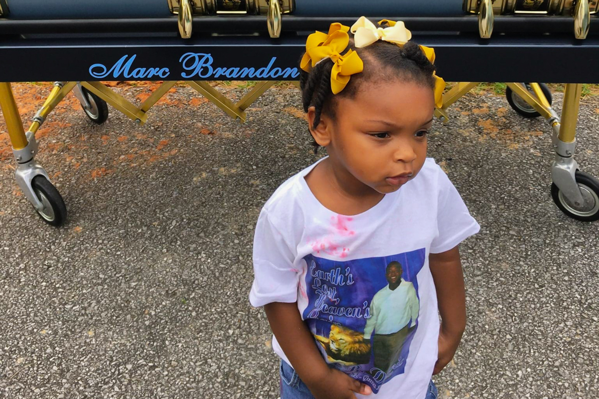 Leah Davis, a small Black child with yellow ribbons in her hair, stands in front of her father's casket in June 2017. She is wearing a white graphic t-shirt with a photograph of her father in the center with pink candy stains around her collar.