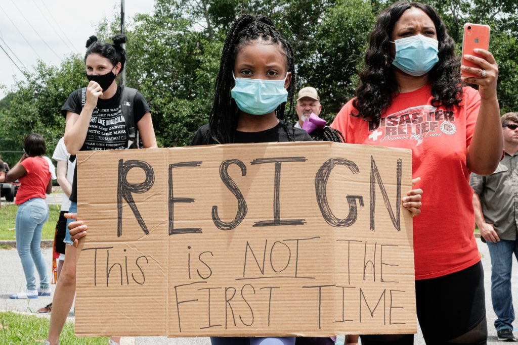 """A young Black girl, wearing a mask, holds a cardboard sign as she stands outside Petal City Hall protesting Mayor Hal Marx for his comments. The sign reads: """"Resign: This is Not the First Time"""""""