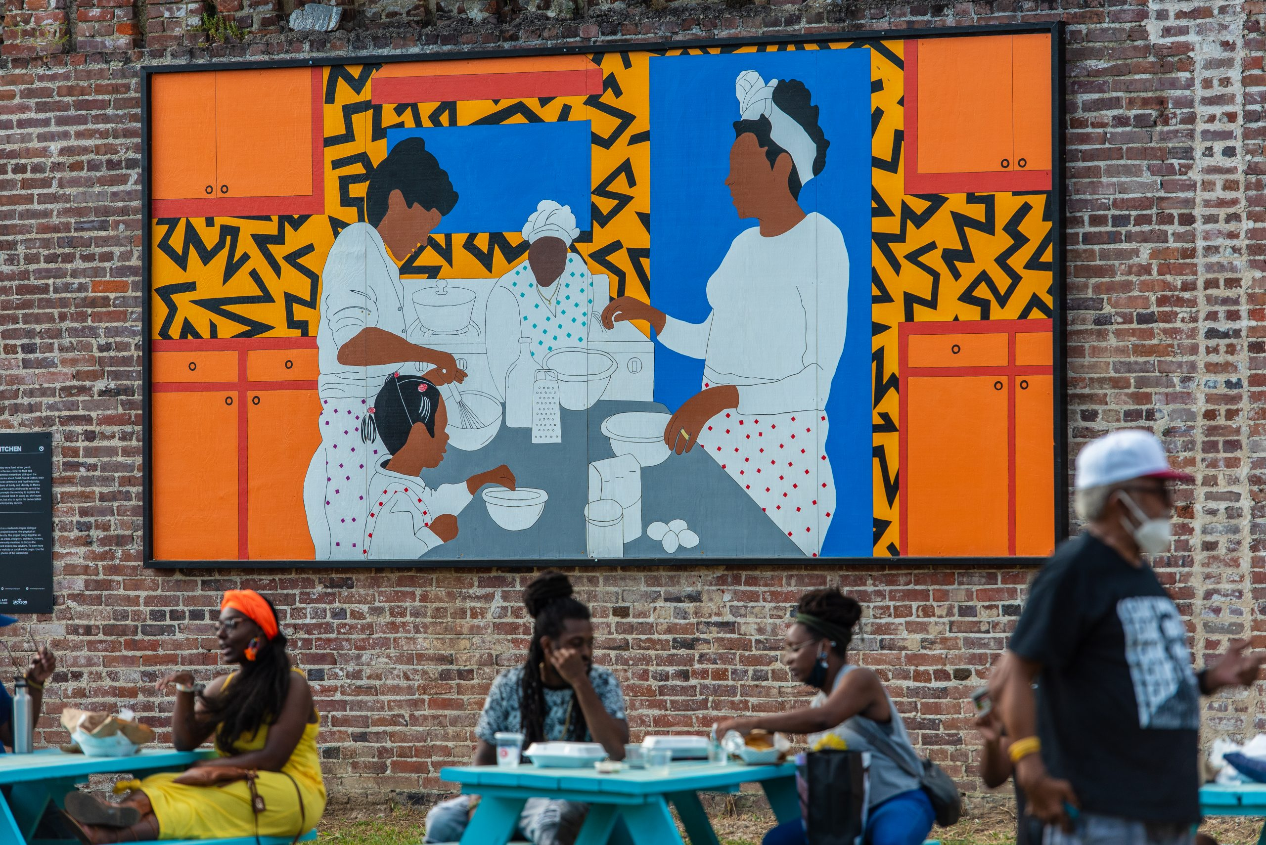 People eating and talking at tables in front of a large mural of a family at a table