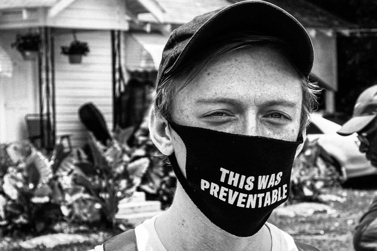 """A white man wears a mask with the words: """"This was preventable"""""""