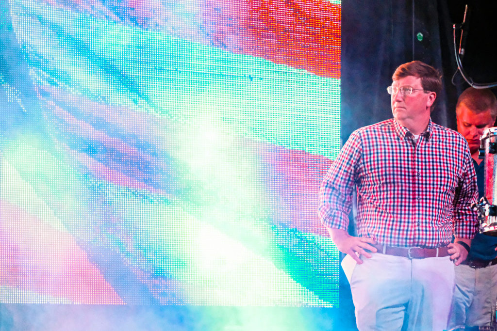 Tate Reeves stand in front of an LED screen with the American flag waving on it