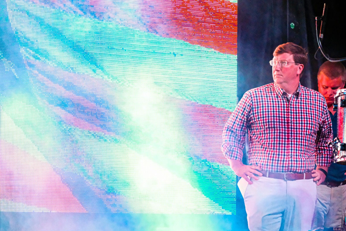 Gov. Tate Reeves stands in front of an LED video screen with an image of an American flag flapping in the wind