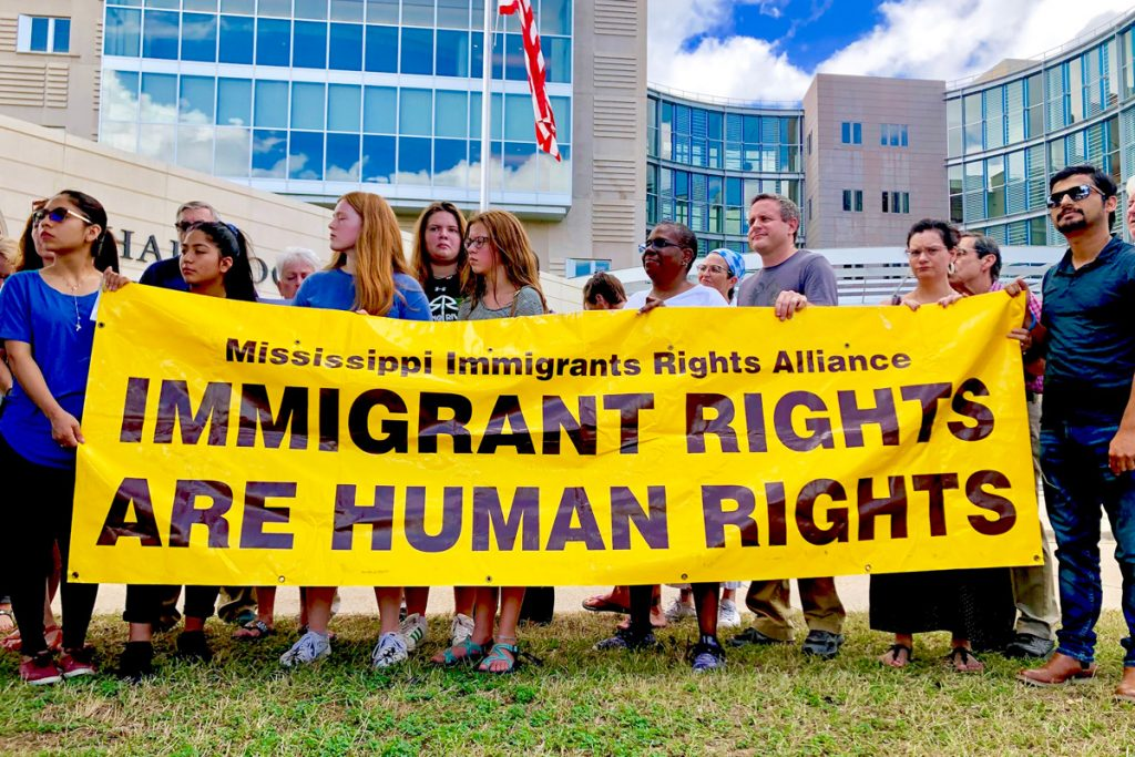 """A dozen supporters of immigrants rights hold a yellow banner saying: """"IMMIGRANT RIGHTS ARE HUMAN RIGHTS"""" outside the federal courthouse in Jackson"""