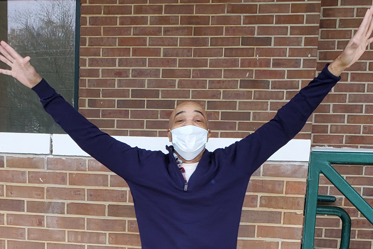 Eddie Lee Howard wearing a blue long sleeve shirt and medical mask with arms raised out