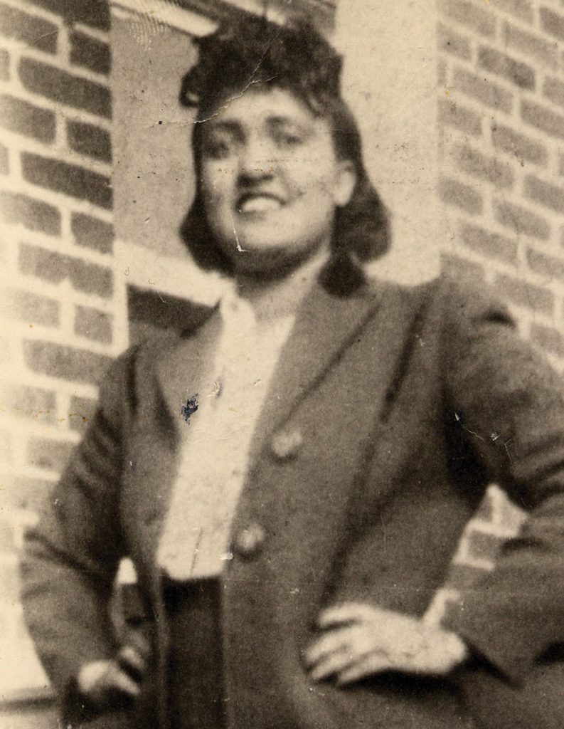 Old photo of a smiling woman in front of a brick wall