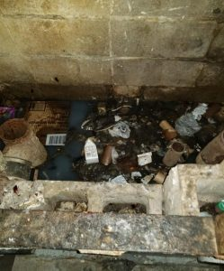 Concrete brick walled sink filled with trash and dirty water