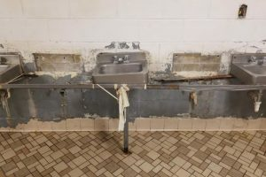 Grey concrete wall with a row of sinks, every other sink is missing and those remaining look damaged