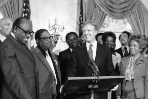 Jimmy Carter at a podium surrounded by people