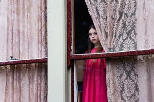 Girl in pink dress looking through pink curtains