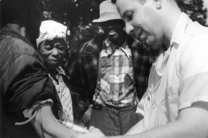 White man injecting a black man while two others watch