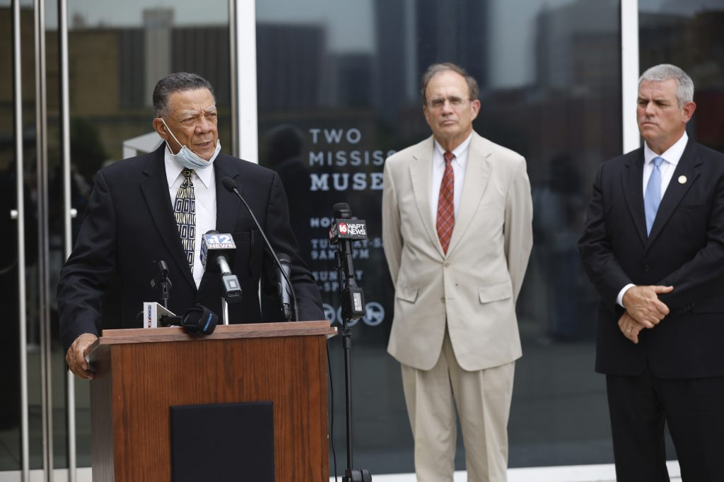 Reuben Anderson speaks at a podium outside the Two Mississippi Museums as Lieutenant Governor Delbert Hosemann and Mississippi House Speaker Philip Gunn look on.