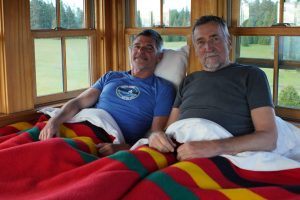 Two men in bed under a bright red blanket