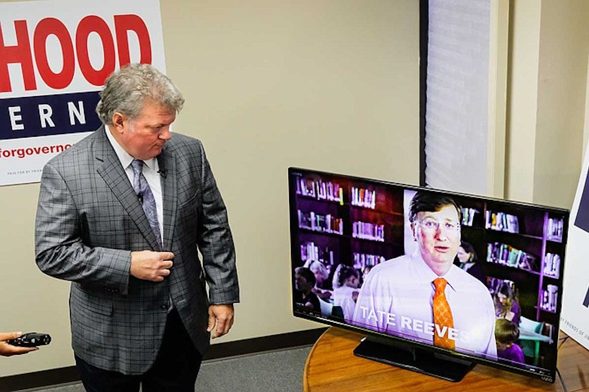 Jim Hood watches a Tate Reeves ad on TV