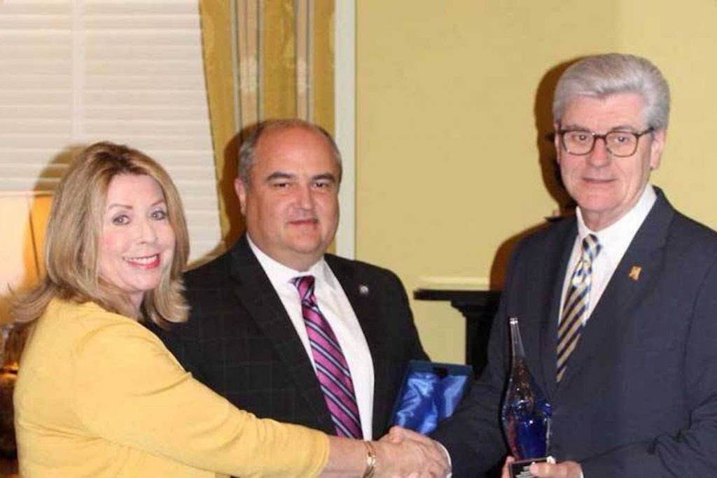 Nancy New shakes hands with Phil Bryant while John Davis stands behind them