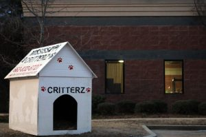 A white doghouse with the Mississippi Critterz name painted on it sits outside the shelter