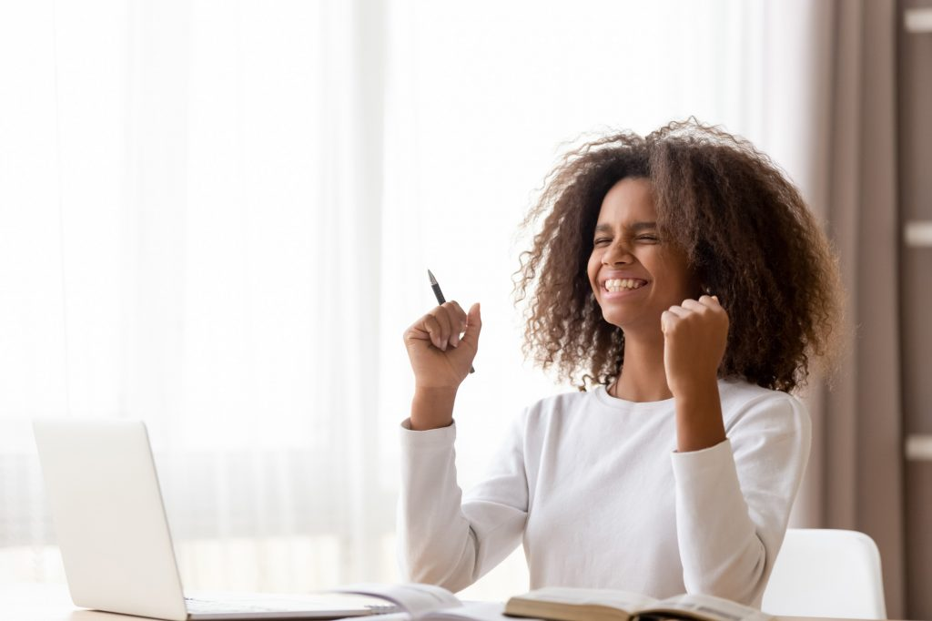 Girl grinning with hands up triumphantly at a desk with laptop and books