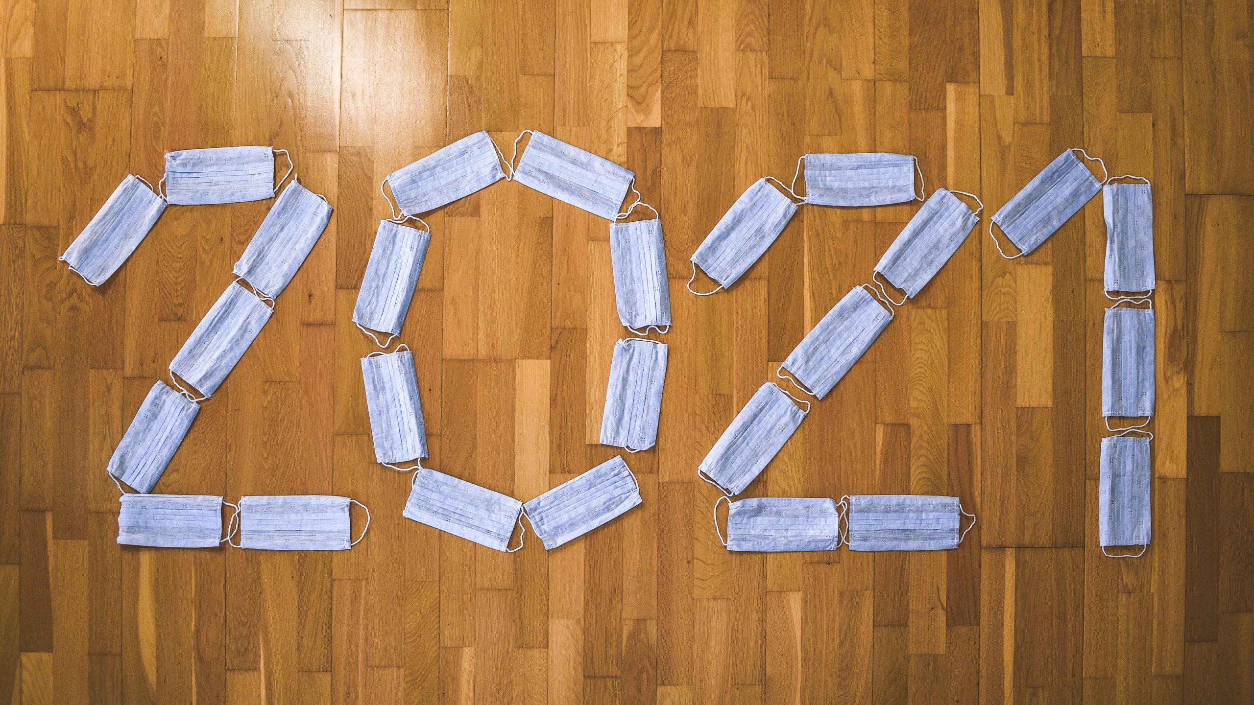 white masks spell out 2021 on hardwood floor
