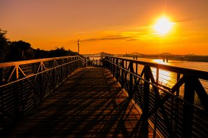 A walkway in Natchez, Mississippi is covered in shadows as the orange sets over the Mississippi River in an orange sky