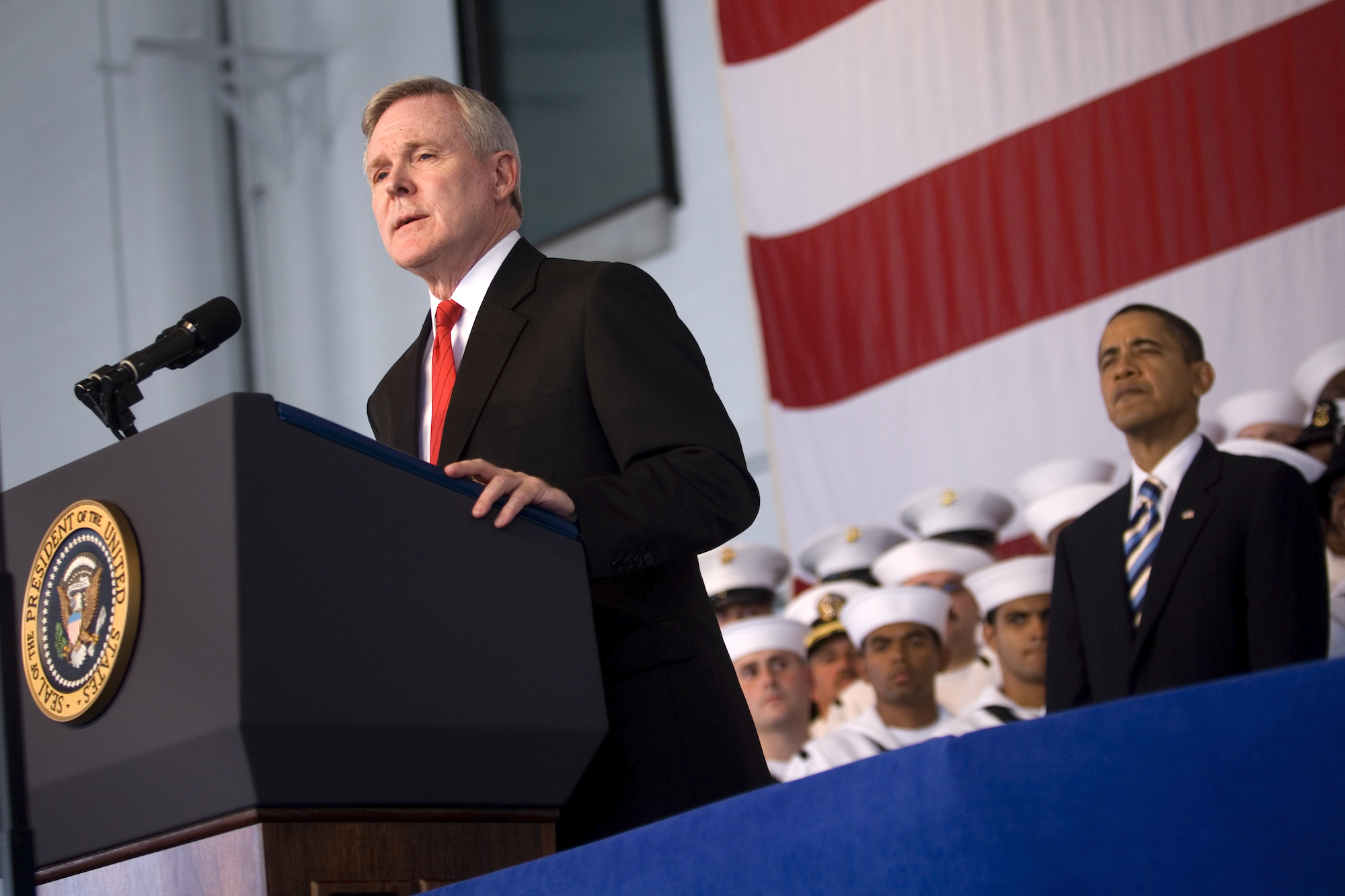 Ray Mabus stands at a podium with president Barack Obama standing behind him