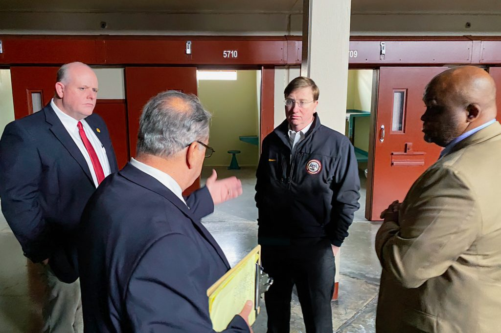 Governor Tate Reeves stands inside Parchman prison with men standing around him