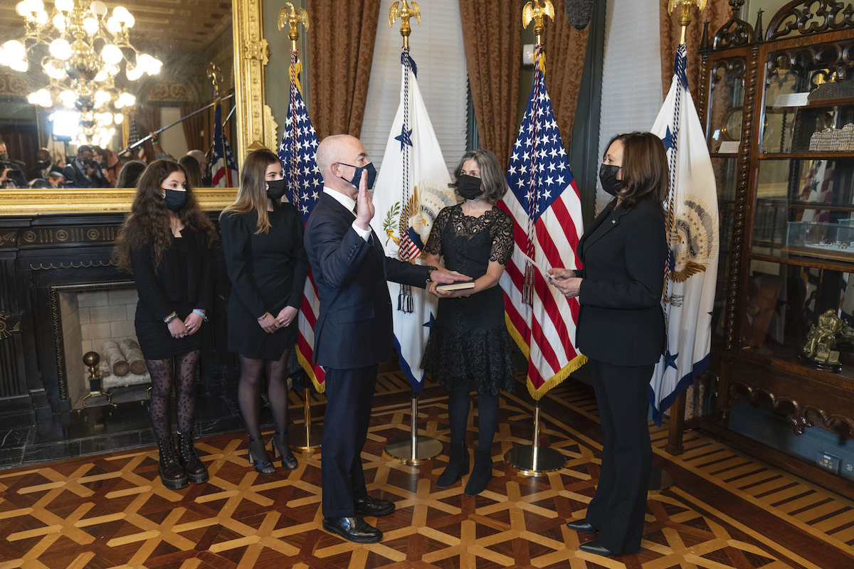 Secretary Mayorkas holds up his hand as he takes the oath of office with Vice President Kamala Harris swearing him in.