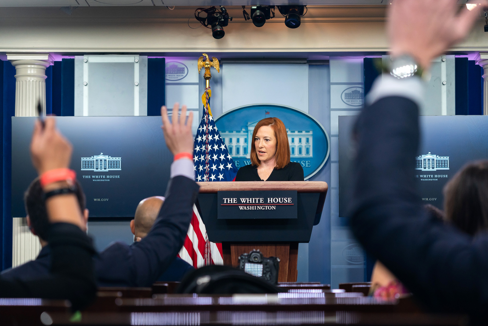 White House Press Secretary Jenn Psaki takes questions while standing at the White House press secretary's podium, journalists' arms raised in front of her