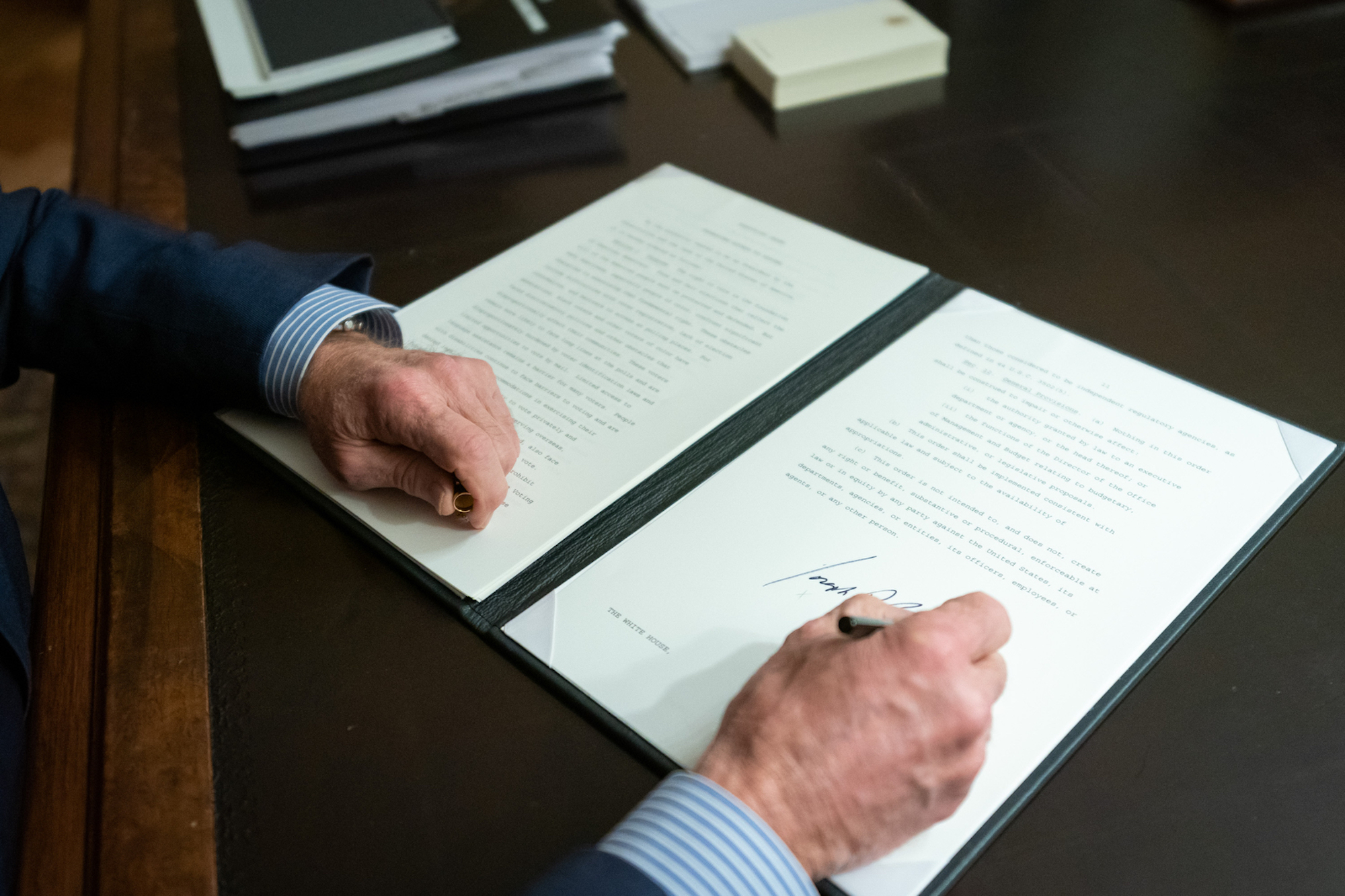 Image shows president Biden's hands as he signs an executive order promoting voting access