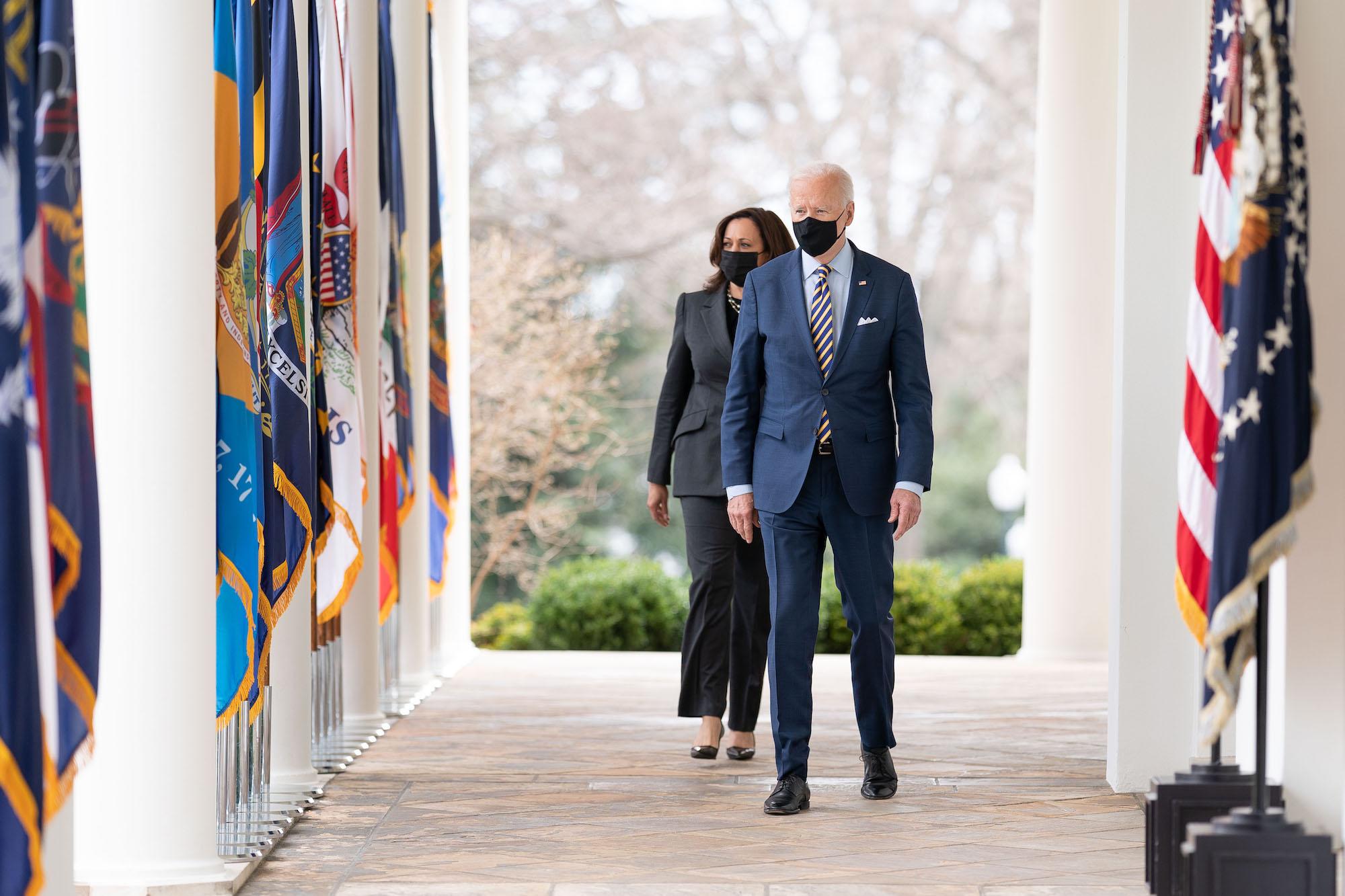 President Biden and Vice President Kamala Harris walk down a breezeway outside the White House