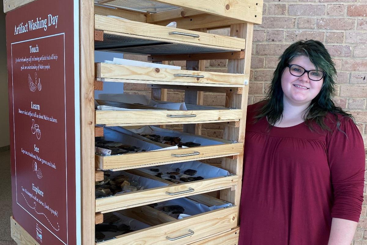 Arianna Kitchens standing beside Artifact Washing Day shelves.