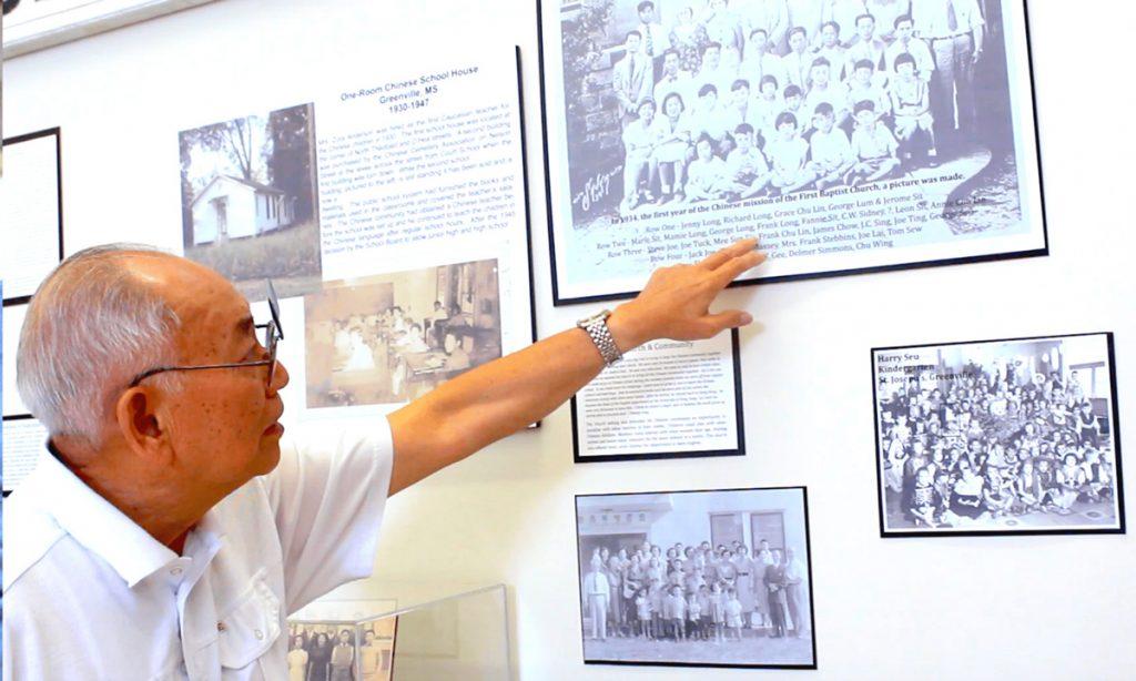 Charles Chiu pointing at old photo