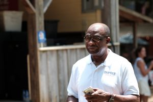 Mayor Johnny DuPree, a Black man, walking at the Neshoba County Fair wearing a white campaign polo shirt with his last name over the pocket
