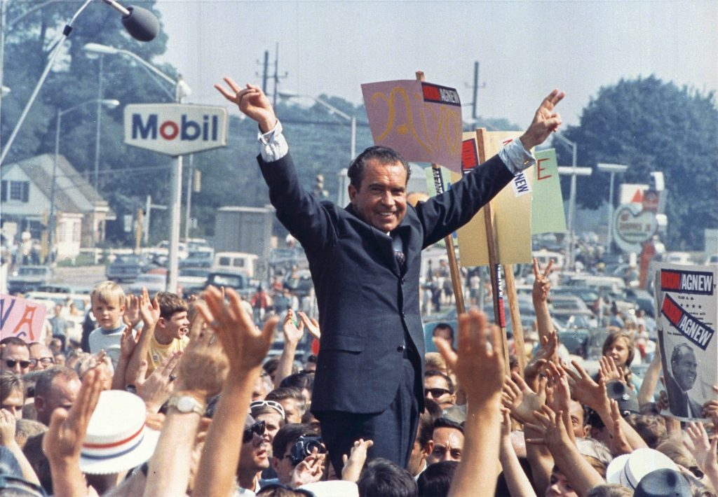 Nixon flashes his victory sign amid a crowd of supporters in 1968