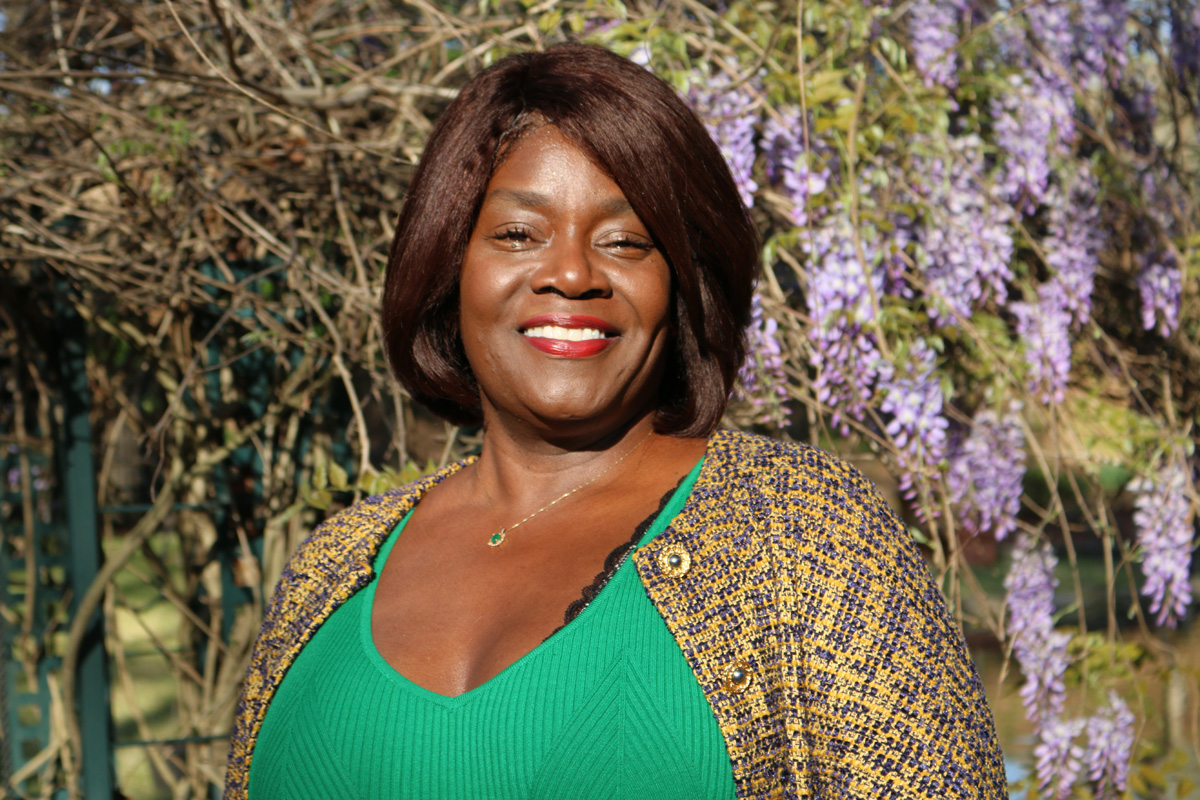 Pam McKelvy Hamner standing in front of wisteria