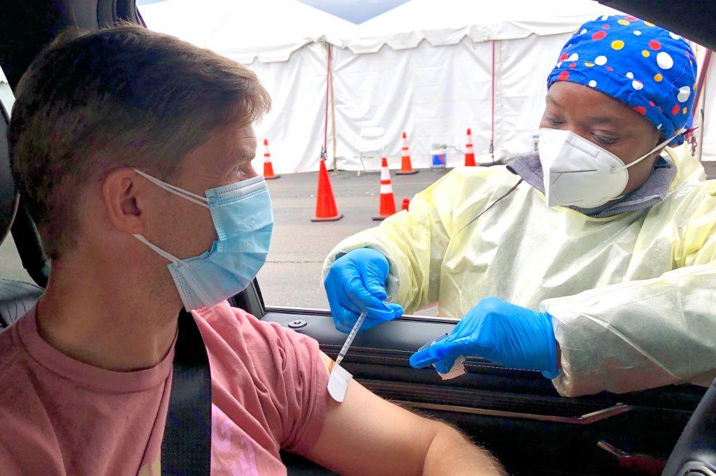 Black woman nurse administering COVID vaccine to white man in drive-thru
