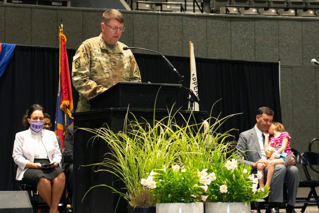 Colonel Terry Partin, in uniform, speaks at the Mississippi National Day of Prayer with Secretary of State Michael Watson behind him with his daughter in his lap