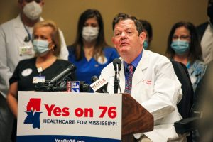 Dr. John Gaudet stands at the podium with nurses and health workers behind him and a YES ON 76 campaign sign in front of him in support of Medicaid expansion