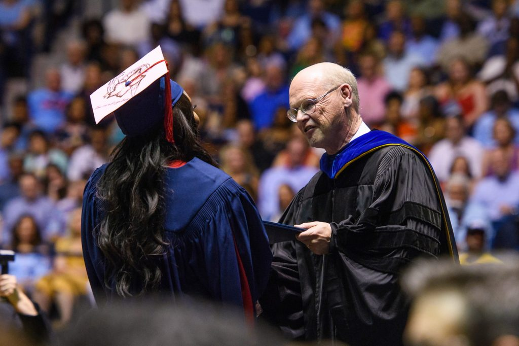 Will Norton, seen here in 2018 as the journalism school dean, hands a diploma to a student at a crowded graduation ceremony