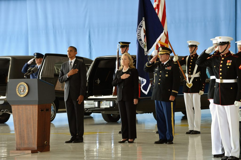 Hillary Clinton and Barack Obama stand alongside marines with hands over hearts at a Transfer of Remains Ceremony for the Benghazi victims