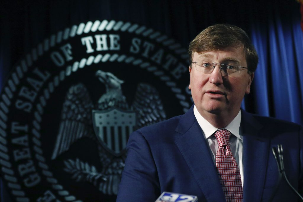 Governor Tate Reeves stands in front of the seal of Mississippi speaking
