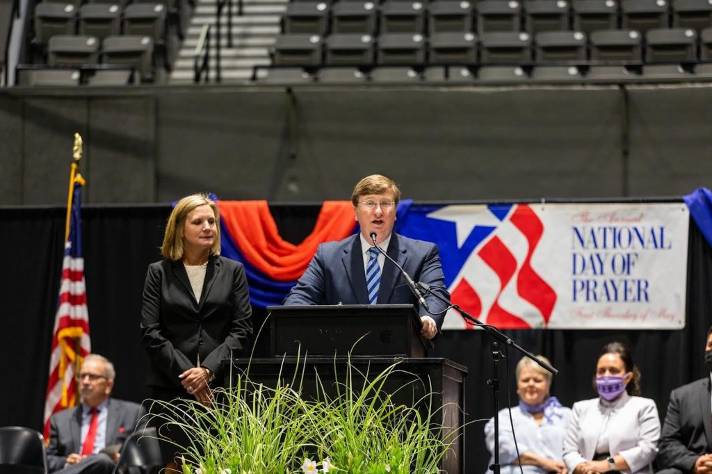 """Governor Reeves stands at a podium in the Mississippi coliseum with wife Elee Reeves next to him and the words """"National Day of Prayer"""" behind him"""