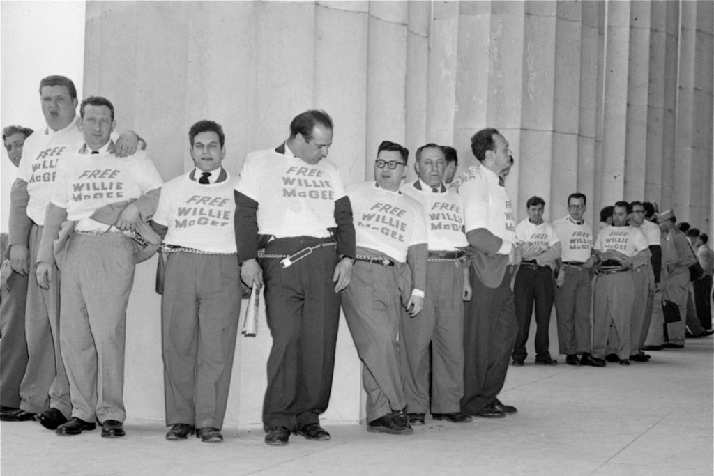 """Men wearing """"Free Willie McGee"""" shirts, chained to the Lincoln Memorial"""