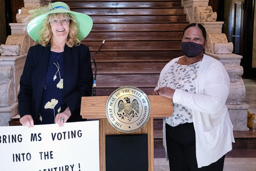 """Kelly Jacobs, wearing a green hat, stands with a sign that reads, """"Bring MS Voting Into the 21st Century"""" next to House Representative Hester Jackson McCray"""