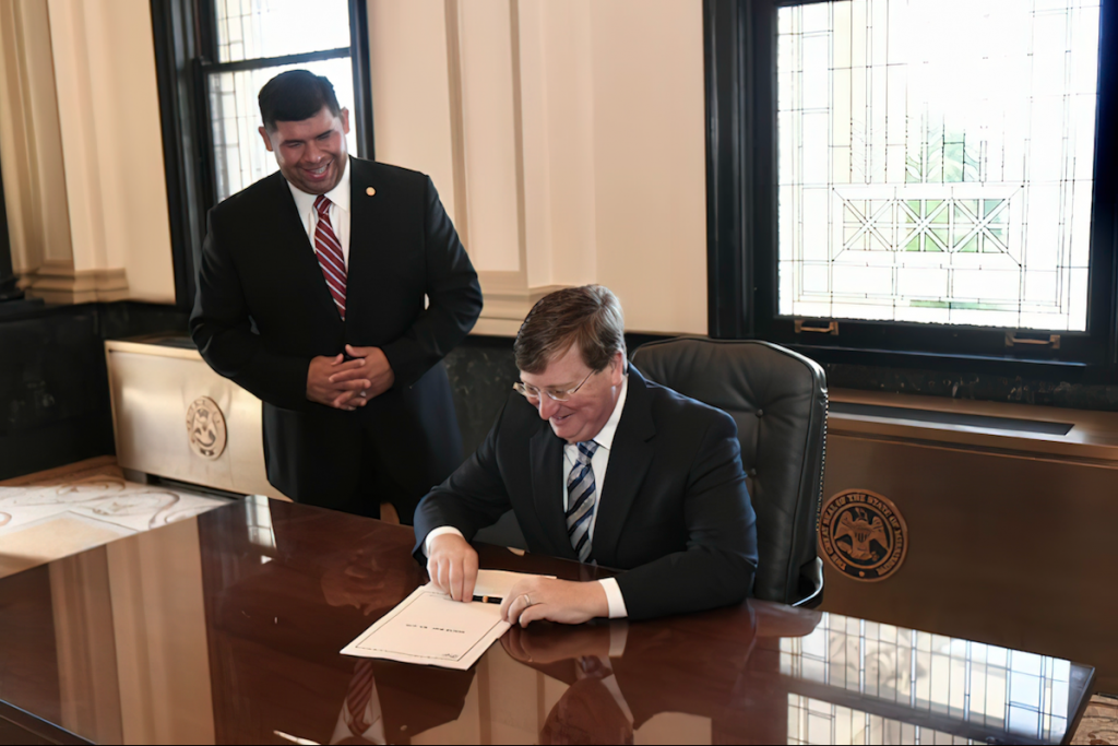 Chief Cyrus Ben and Governor Tate Reeves grin as the governor signs bills into law aimed at helping the Choctaw Band of Mississippi Indians