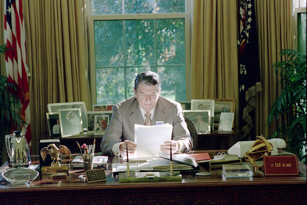 Ronald Reagan sits at the Resolute Desk working
