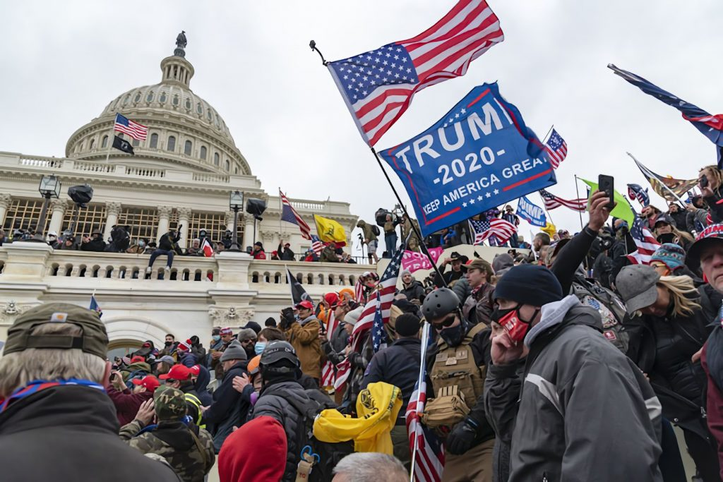 Trump supporters carrying Trump flags and American flags scale the walls of the U.S. Capitol
