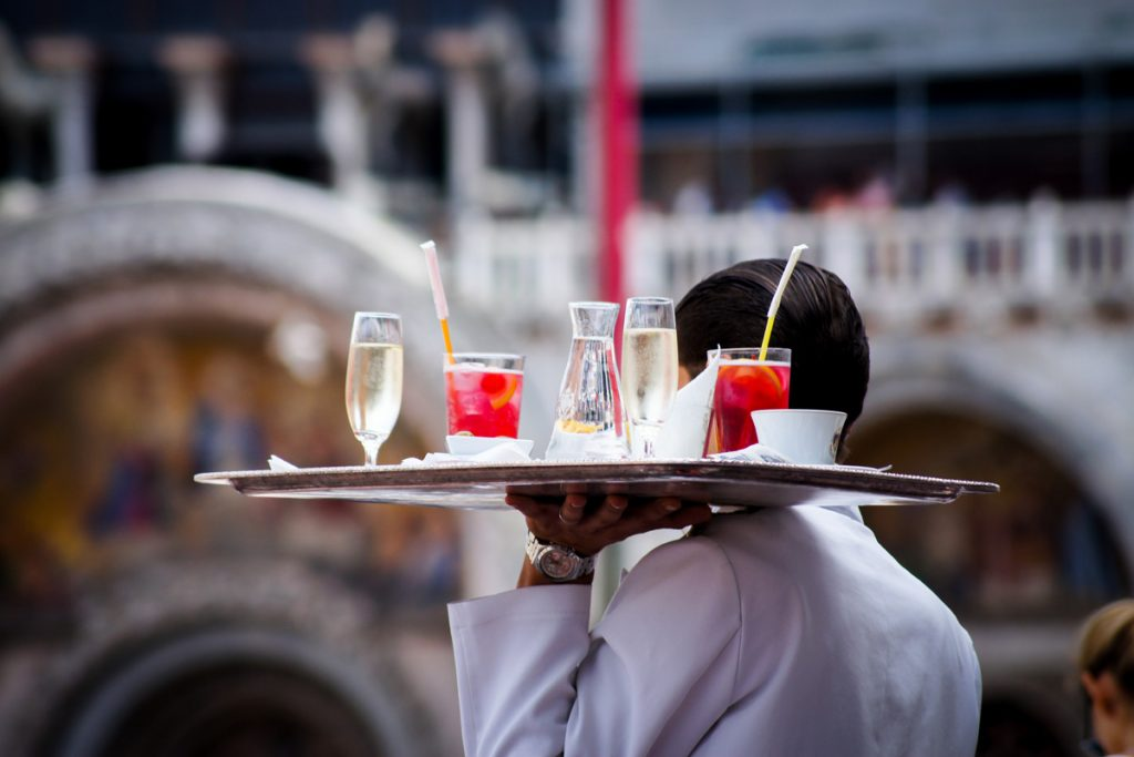 Waiter with a tray holding drinks