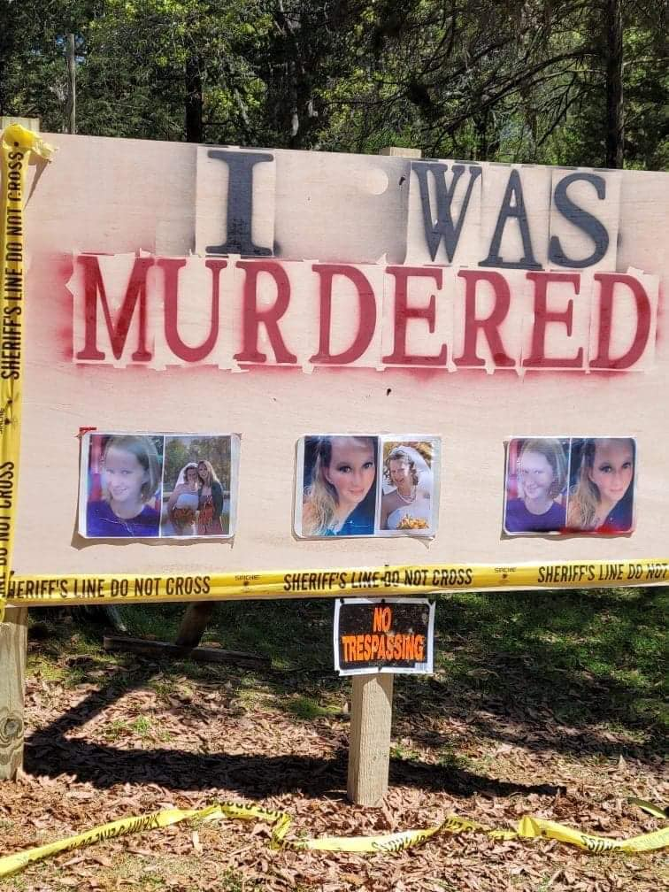 """A makeshift billboard includes the words """"I WAS MURDERED"""" and photos of Kristina Michelle Jones"""