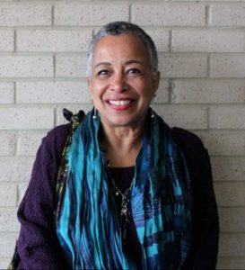 Barbara Phillips stands in front of a white brick wall wearing a long turquoise scarp. The Black woman's graying hair is cropped short