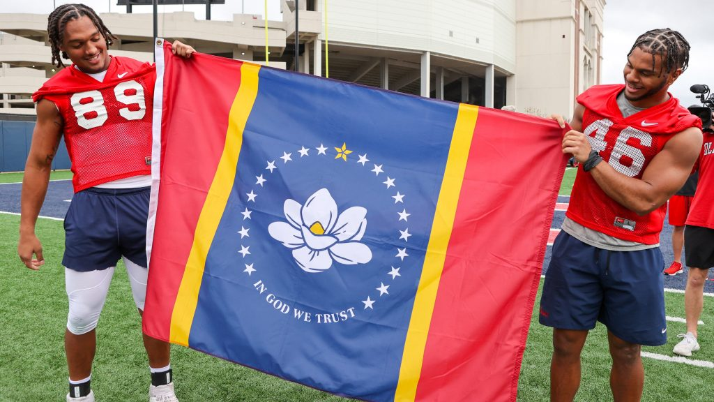 Two men hold up a new mississippi state flag